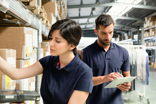 Warehouse workers using digital tablet to prepare order in distribution warehouseの写真素材 [FYI03533096]
