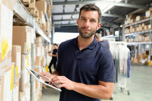Warehouse worker using digital tablet in distribution warehouseの写真素材 [FYI03533097]