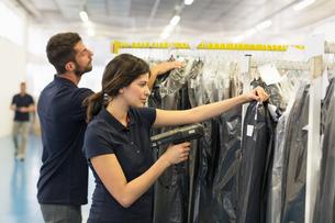 Warehouse worker preparing garment order in distribution warehouseの写真素材 [FYI03533101]