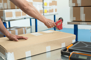 Hands of warehouse worker taping parcel in distribution warehouseの写真素材 [FYI03533109]