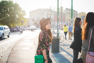 Young woman strolling behind friends in cityの写真素材 [FYI03533194]
