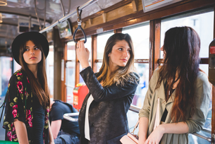 Three young women travelling on city tramの写真素材 [FYI03533210]