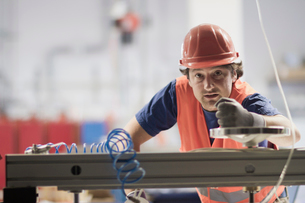Mid adult man wearing hard hat looking at camera, operating machineの写真素材 [FYI03533391]