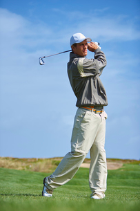 Full length front view of golfer holding golf club taking golf swingの写真素材 [FYI03533586]