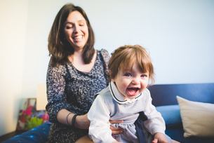 Female toddler sitting on mothers lap playingの写真素材 [FYI03533644]