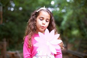 Girl blowing flower pinwheel at garden birthday partyの写真素材 [FYI03533793]