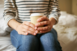 Womans hands holding takeaway coffee on bedの写真素材 [FYI03533824]