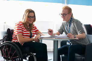 Teacher and female student in wheelchair having classroom tutorialの写真素材 [FYI03533880]