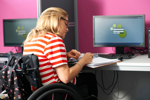 Teenage girl in wheelchair writing up file notes in classの写真素材 [FYI03533884]