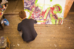 Young man painting on canvas in studioの写真素材 [FYI03534248]