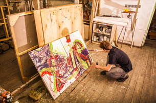 Young man painting on canvas in studioの写真素材 [FYI03534252]