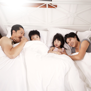 Young Chinese family of parents and two young children laying in bed together at homeの写真素材 [FYI03534377]