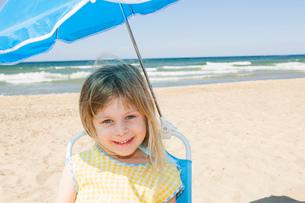 Portrait of girl in parasol shade on beachの写真素材 [FYI03534710]