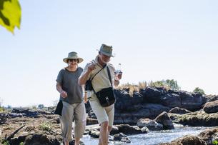 Senior man and wife exploring river rocks, near Victoria Falls, Zambiaの写真素材 [FYI03534760]