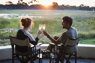 Couple making wine toast at sunset at safari lodge, Kafue National Park, Zambiaの写真素材 [FYI03534801]