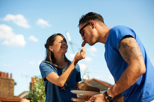 Mid adult woman feeding sausage to boyfriend at rooftop partyの写真素材 [FYI03534832]