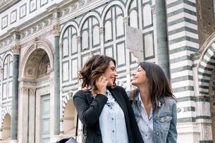 Lesbian couple using mobile phone face to face smiling, Piazza Santa Maria Novella, Florence, Tuscanの写真素材 [FYI03534929]