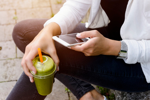 Cropped shot of young woman sitting with smoothie drink using smartphoneの写真素材 [FYI03535056]