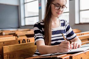 Female student working in empty classroomの写真素材 [FYI03535167]