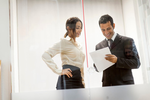 Businessman and businesswoman looking at documents, having conversationの写真素材 [FYI03535307]