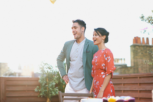 Mid adult couple standing on roof terrace looking away smiling, mouth openの写真素材 [FYI03535336]