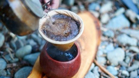 キャンプ場でコーヒーをドリップするの写真素材 [FYI03535354]