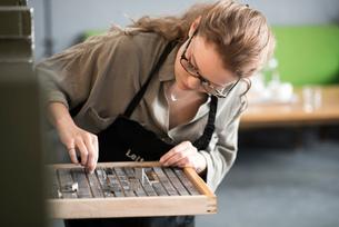 Woman choosing letterpress from tray in print workshopの写真素材 [FYI03535377]