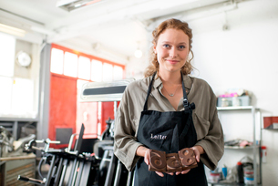 Portrait of young woman with wooden letterpress in print workshopの写真素材 [FYI03535378]