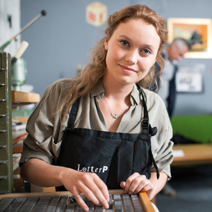 Portrait of young woman with letterpress tray in print workshopの写真素材 [FYI03535379]