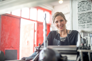 Portrait of female printer with traditional letterpress print machine in workshopの写真素材 [FYI03535381]