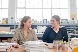 Female print designers talking in workshopの写真素材 [FYI03535401]