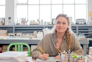 Portrait of female print designer working on sketchbook in workshopの写真素材 [FYI03535403]