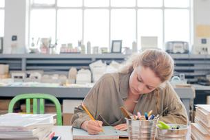 Female print designer working on sketchbook in workshopの写真素材 [FYI03535404]