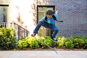 Boy doing skateboarding trick jump on urban sidewalkの写真素材 [FYI03535552]