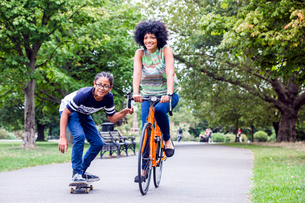 Skateboarding boy holding onto mothers bicycle in parkの写真素材 [FYI03535568]
