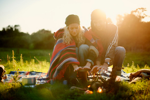 Young camping couple warming hands by campfire at duskの写真素材 [FYI03535746]