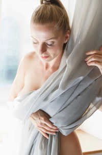 Mid adult woman, nude, covering body with curtainの写真素材 [FYI03535800]