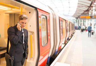 Businessman using phone, Underground station, London, UKの写真素材 [FYI03536244]