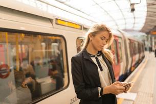 Business woman texting on platform, Underground station, London, UKの写真素材 [FYI03536245]