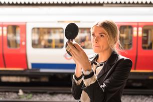 Businesswoman applying make up, London Underground, UKの写真素材 [FYI03536260]