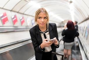 Businesswoman texting on escalator, London Underground, UKの写真素材 [FYI03536268]