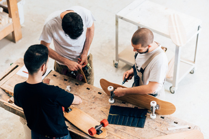 High angle view of young men standing around workbench attaching wheels to skateboardsの写真素材 [FYI03536364]