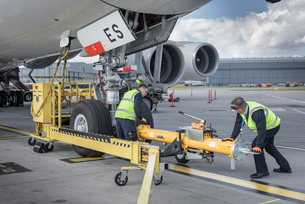 Ground crew fixing tow bar onto A380 aircraft at airportの写真素材 [FYI03536452]