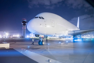 Engineer communicating with pilot of A380 aircraft on runway at nightの写真素材 [FYI03536673]