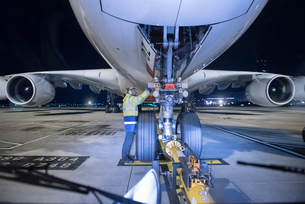 Chief engineer inspecting A380 aircraft on runway at airport at nightの写真素材 [FYI03536676]