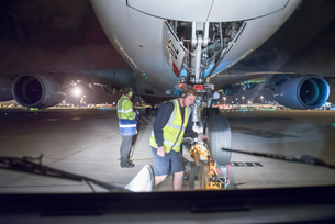 Ground crew uncoupling tug A380 aircraft on runway at nightの写真素材 [FYI03536679]