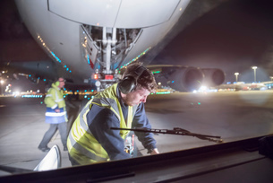 Ground crew uncoupling tug A380 aircraft on runway at nightの写真素材 [FYI03536681]