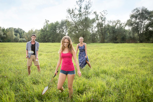 Group of young adults playing badminton in fieldの写真素材 [FYI03536722]