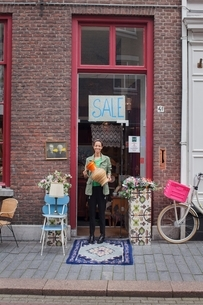 Portrait of young female customer holding jug outside vintage shopの写真素材 [FYI03536887]
