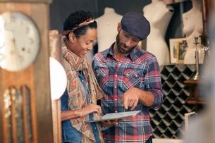 Male customer checking digital tablet online in vintage shopの写真素材 [FYI03536903]
